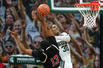 Michigan State forward Marcus Bingham Jr. (30) drives on Nebraska forward Derrick Walker (13) in the first half of an NCAA college basketball game in East Lansing, Mich., Saturday, Feb. 6, 2021. (AP Photo/Paul Sancya)