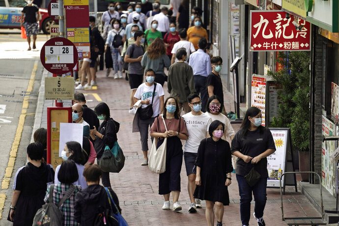 FILE - In this Oct. 9, 2020, file photo, people wearing masks to protect against the coronavirus, walk down a street in Hong Kong. Singapore and Hong Kong have postponed a planned air travel bubble meant to boost tourism for both cities, amid a spike in coronavirus infections in Hong Kong. The air travel bubble, originally slated to begin Sunday, will be delayed by at least two weeks, Hong Kong's minister of commerce and economic development, Edward Yau, said at a news conference on Saturday, Nov. 21, 2020. (AP Photo/Kin Cheung, File)