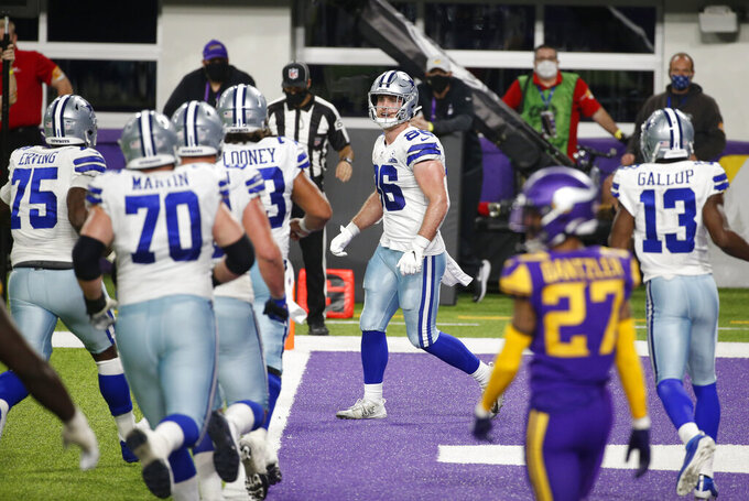Dallas Cowboys tight end Dalton Schultz, center, celebrates with teammates after catching a 2-yard touchdown pass during the second half of an NFL football game against the Minnesota Vikings, Sunday, Nov. 22, 2020, in Minneapolis. The Cowboys won 31-28. (AP Photo/Bruce Kluckhohn)