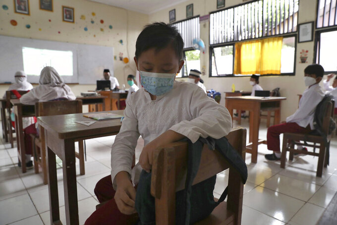 Students wearing face masks sit spaced apart during a trial run of a class with COVID-19 protocols at an elementary school in Jakarta, Indonesia, Friday, June 4, 2021. The world's fourth-most populous country, with about 275 million people, has reported more coronavirus cases than any other Southeast Asian country. (AP Photo/Tatan Syuflana)