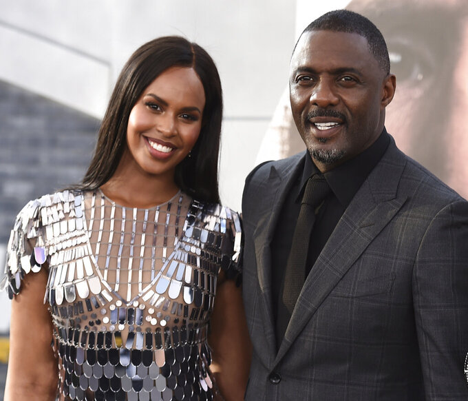 """FILE - In a Saturday, July 13, 2019 file photo, cast member Idris Elba, center, arrives with his wife Sabrina Dhowre Elba, left, and Isan Elba, right, at the Los Angeles premiere of """"Fast & Furious Presents: Hobbs & Shaw"""", at the Dolby Theatre. Idris Elba says he and his wife had their lives """"turned around"""" after contracting the coronavirus. (Photo by Jordan Strauss/Invision/AP, File)"""