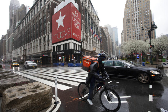 A cyclist passes Macy's in Herald Square, Monday, March 23, 2020, in New York. Macy's stores nationwide are closed due to the coronavirus. (AP Photo/Mark Lennihan)