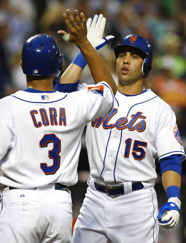 FILE - In this Tuesday, June 9, 2009 file photo, New York Mets Alex Cora (3) greets Carlos Beltran at the plate after Beltran's third-inning two-run home run off Philadelphia Phillies pitcher J.A. Happ in a baseball game at Citi Field in New York. While the Houston Astros and Boston Red Sox took decisive action in jettisoning their managers after Major League Baseball concluded they were involved in nefarious sign stealing, the New York Mets have stayed silent on Carlos Beltrán's future. (AP Photo/Kathy Willens, File)