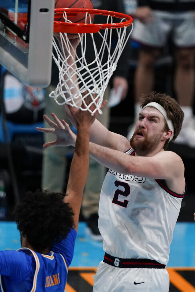 Gonzaga forward Drew Timme (2) drives to the basket over UCLA guard Johnny Juzang, left, and guard Jaime Jaquez Jr., right, during the second half of a men's Final Four NCAA college basketball tournament semifinal game, Saturday, April 3, 2021, at Lucas Oil Stadium in Indianapolis. (AP Photo/Michael Conroy)