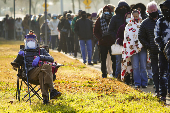 FILE - In this Jan. 11, 2021, file photo, Florence Mullins, 89, sits in a chair as a family member holds her place in a long line to receive a COVID-19 vaccine at Fair Park in Dallas. Uncertainty over the pace of federal COVID-19 vaccine allotments triggered anger and confusion Friday, Jan. 15, 2021, in some states where officials worried that expected shipments would not be forthcoming.  (Smiley N. Pool/The Dallas Morning News via AP)