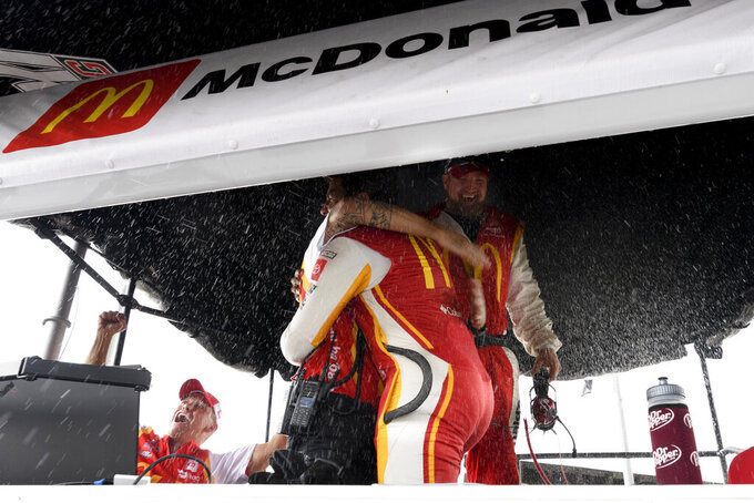 Bubba Wallace and crew react after he is pronounced the winner while waiting out a rain delay before which he was the leader during a NASCAR Cup series auto race Monday, Oct. 4, 2021, in Talladega, Ala. (AP Photo/John Amis)