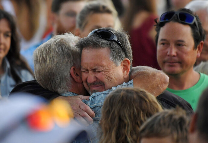 Glen Fritzler, left, co-owner of Truth Aquatics and the dive boat Conception, consoles an attendee during a vigil Friday, Sept. 6, 2019, in Santa Barbara, Calif., for the victims who died aboard the dive boat Conception. The Sept. 2 fire took the lives of 34 people on the ship off Santa Cruz Island off the Southern California coast near Santa Barbara. (AP Photo/Mark J. Terrill)
