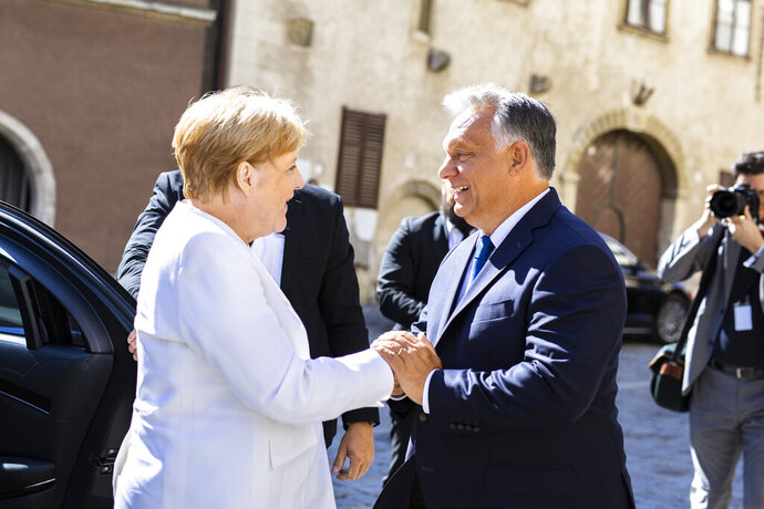 In this handout photo provided by the Hungarian Prime Minister's Press Office Hungarian Prime Minister Viktor Orban, right, welcomes German Chancellor Angela Merkel in Sopron, Hungary, Monday, Aug. 2019. Merkel arrived for the 30th anniversary of the beginning of the dismantling of the iron curtain between Hungary and Austria. (Balazs Szecsodi/Hungarian Prime Minister's Press Office/MTI via AP)