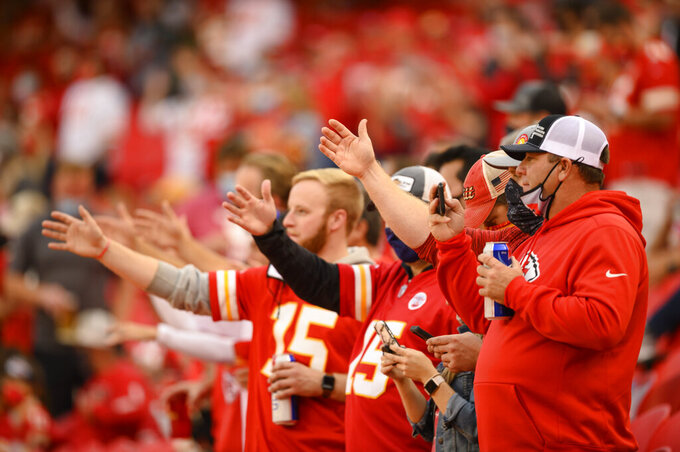 "FILE - In this Oct. 5, 2020, file photo, Kansas City Chiefs fans do ""the chop"" at the start of the team's NFL football game against the New England Patriots in Kansas City, Mo. The Chiefs barred headdresses and war paint amid the nationwide push for racial justice, but its effort to make its popular ""war chant"" more palatable is getting a fresh round of scrutiny from Native American groups as the team prepares to make its second straight Super Bowl appearance. (AP Photo/Reed Hoffmann, File)"