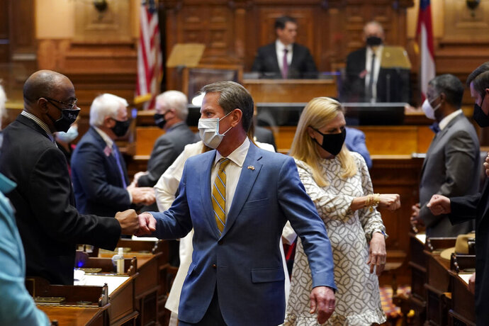 Georgia Gov. Brian Kemp and his wife Marty fist bump lawmakers as they leave the House Chamber after Kemp delivered his State of the State address Thursday, Jan. 14, 2021, in Atlanta. (AP Photo/John Bazemore)