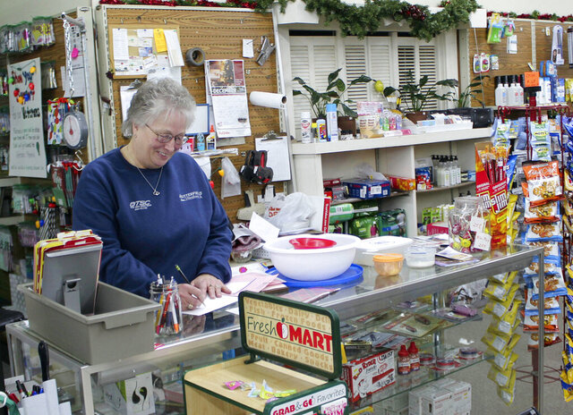 In this Tuesday, Dec. 17, 2019 photo, Barb Mathistad Warner, co-owner of the True Value Hardware store in Butterfield, Minn., counts down the cash register at the end of business hours. Since the southern Minnesota town lost its grocery store a decade ago, Barb and her husband, Mark Warner, decided to offer groceries as a part of their services to the community. (Hannah Yang/Minnesota Public Radio via AP)