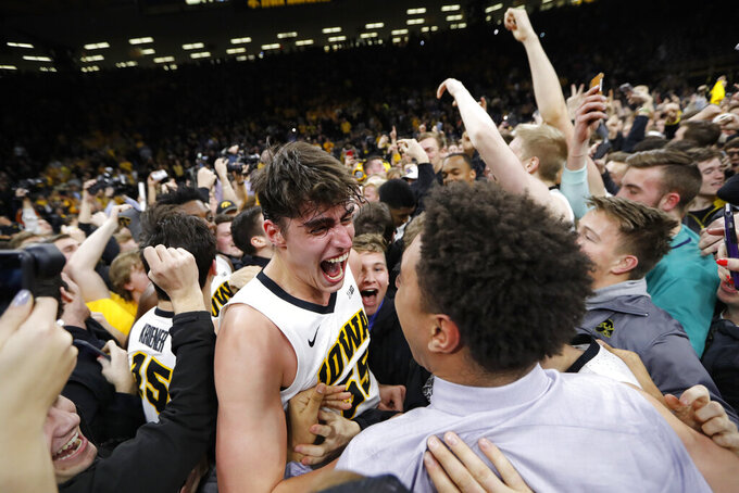 Iowa forward Luka Garza, center, celebrates with teammate Cordell Pemsl, right, after the team's NCAA college basketball game against Michigan, Friday, Feb. 1, 2019, in Iowa City, Iowa. Garza scored 19 points as Iowa won 74-59. (AP Photo/Charlie Neibergall)