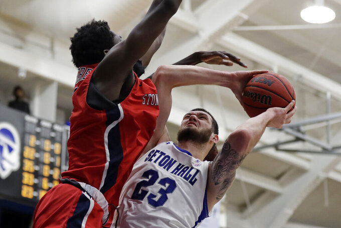 Seton Hall forward Sandro Mamukelashvili (23) drives to the basket defended by Stony Brook guard Tavin Pierre Philippe during the second half of an NCAA college basketball game, Saturday, Nov. 9, 2019, in South Orange, N.J. Seton Hall won 74-57. (AP Photo/Adam Hunger)