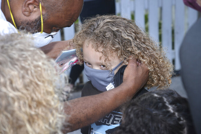 Michael Curtis gets help putting on his mask from his father Richard Curtis before entering Alcoa Elementary School Wednesday morning, July 22,2020 in Alcoa Tenn. (Scott Keller/The Daily Times via AP)