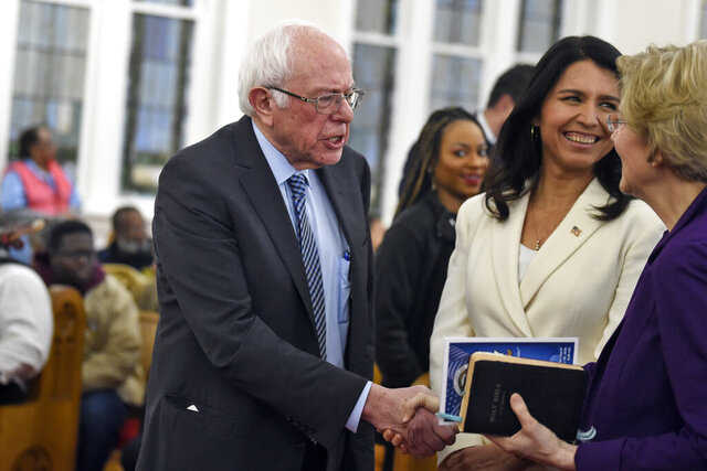 Democratic presidential candidates US. Sen. Bernie Sanders, left, I-Vt. and Sen. Elizabeth Warren, right, D--Mass., shake hands as greets U.S. Rep. Tulsi Gabbard, center, D-Hawaii at a Martin Luther King Jr. Day services at Zion Baptist Church, Monday, Jan. 20, 2020, in Columbia, S.C. (AP Photo/Meg Kinnard)