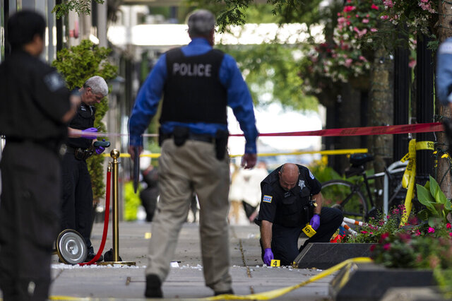 Chicago police investigate the scene where three people were shot, one of them fatally, in the Gold Coast neighborhood of the Chicago, Tuesday, Aug. 4, 2020. (Tyler LaRiviere/Chicago Sun-Times via AP)