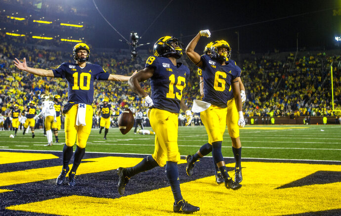 Michigan wide receiver Mike Sainristil (19) celebrates his 26-yard touchdown reception from Michigan quarterback Dylan McCaffrey (10), alongside wide receiver Cornelius Johnson (6) in the fourth quarter of an NCAA college football game against Notre Dame in Ann Arbor, Mich., Saturday, Oct. 26, 2019. Michigan won 45-14. (AP Photo/Tony Ding)