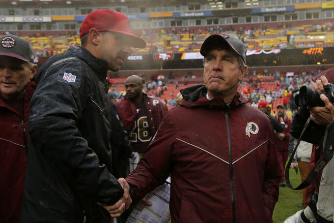 Washington Redskins interim head coach Bill Callahan, right, shakes hands with San Francisco 49ers head coach Kyle Shanahan after an NFL football game, Sunday, Oct. 20, 2019, in Landover, Md. San Francisco won 9-0. (AP Photo/Julio Cortez)