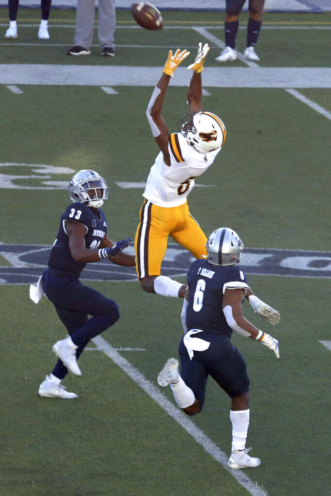 Wyoming State wide receiver Isaiah Neyor (5) catches a first-down pass against Nevada defenders in the first half of an NCAA college football game Saturday, Oct. 24, 2020, in Reno, Nev. (AP Photo/Lance Iversen)