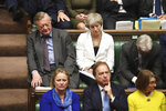Former Prime Minister Theresa May, top centre, and Father of the House lawmaker Ken Clarke, listen to Britain's Prime Minister Boris Johnson as he gives a statement to lawmakers inside the House of Commons to update details of his new Brexit deal with EU, in London Saturday Oct. 19, 2019. At a rare weekend sitting of Parliament, Johnson implored legislators to ratify the Brexit deal he struck this week with the other 27 EU leaders. (Jessica Taylor/House of Commons via AP)