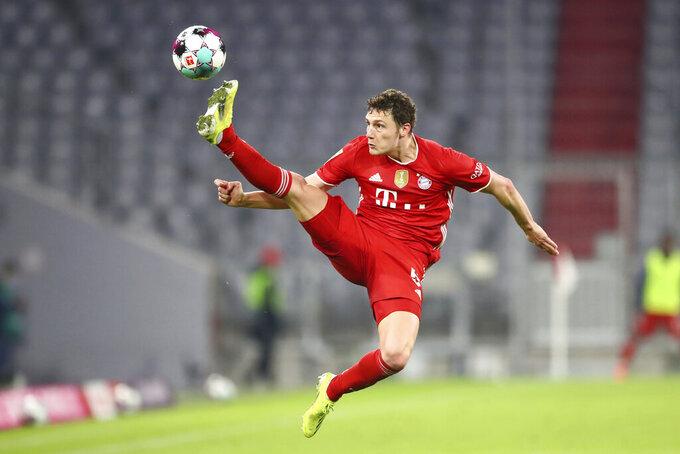 Bayern's Benjamin Pavard tries to control the ball during the German Bundesliga soccer match between Bayern Munich and Bayer Leverkusen at the Allianz Arena stadium in Munich, Germany, Tuesday, April 20, 2021. (AP Photo/Matthias Schrader, Pool)