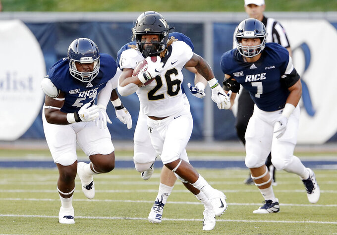 Wake Forest running back Christian Beal-Smith (26) makes a gain between Rice defensive end JaVante Hubbard (52) and defensive end Trey Schuman (7) during the first half of an NCAA college football game Friday, Sept. 6, 2019, in Houston. (AP Photo/Michael Wyke)