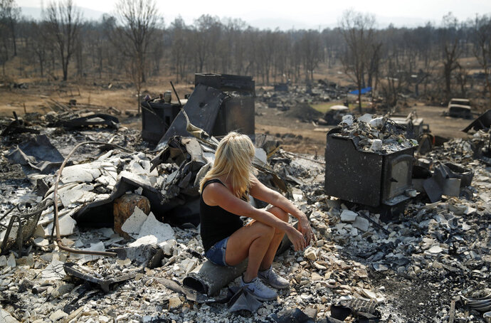 Diana Hartman sits while helping to sift through the charred remains of her mother-in-law's home that was burned in the Carr Fire, Saturday, Aug. 11, 2018, in Redding, Calif. (AP Photo/John Locher)