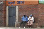 People are seen outside a prayer centre in Harare, Thursday May 28, 2020. Manhunts have begun after hundreds of people, some with the coronavirus, fled quarantine centres in Zimbabwe and Malawi while authorities worry they will spread COVID-19 in countries whose health systems can be rapidly overwhelmed.(AP Photo/Tsvangirayi Mukwazhi)