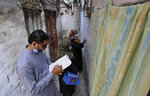 A health worker collects data while another writes numbers on the wall of a house after administrating a polio vaccine to children in a neighborhood of Lahore, Pakistan, Monday, Aug. 2, 2021. The government launched polio vaccination drives across Pakistan in efforts to eradicate the crippling disease by the end of the year. (AP Photo/K.M. Chaudhry)