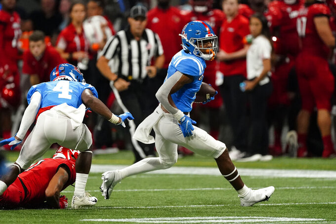 Mississippi wide receiver Dannis Jackson, right, runs after intercepting a pass from Louisville quarterback Malik Cunningham in the first half of an NCAA college football game, Monday, Sept. 6, 2021, in Atlanta. (AP Photo/John Bazemore)