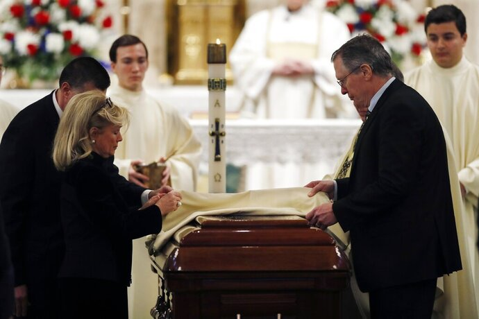 Congresswoman Debbie Dingell, left, and Christopher Dingell place the pall on the casket of John Dingell at the Church of the Divine Child, Tuesday, Feb. 12, 2019, in Dearborn, Mich. Dingell, the longest-serving member of Congress in American history, was first elected in 1955 and retired in 2014. The Democrat was 92 when he passed. (AP Photo/Carlos Osorio)