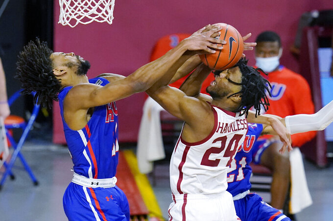 Oklahoma guard Elijah Harkless (24) is fouled by Houston Baptist forward Jason Thompson, left, in the first half of an NCAA college basketball game Saturday, Dec. 19, 2020, in Norman, Okla. (AP Photo/Sue Ogrocki)