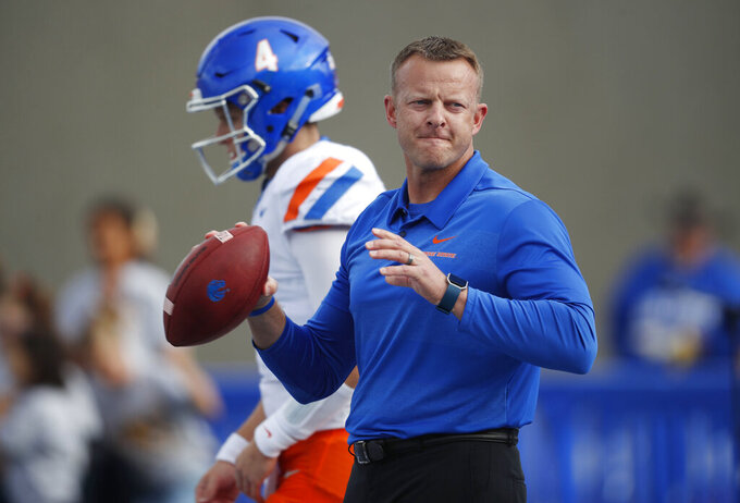 FILE - In this Saturday, Oct. 27, 2018, file photograph, Boise State head coach Bryan Harsin throws passes to receivers in front of quarterback Brett Rypien before an NCAA college football game against Air Force at Air Force Academy, Colo. This season, the Broncos don't have reliable quarterback Brett Rypien. He's with another rendition of the Broncos after signing as an undrafted free agent with Denver. For a change, coach Bryan Harsin is breaking in a new QB.  (AP Photo/David Zalubowski, File)