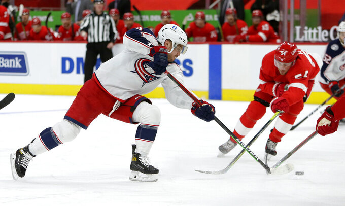Columbus Blue Jackets center Max Domi (16) takes a shot on goal against Detroit Red Wings right wing Bobby Ryan (54) during the third period of an NHL hockey game Tuesday, Jan. 19, 2021, in Detroit. (AP Photo/Duane Burleson)