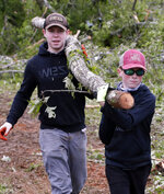 Justus Harvey, 16, left, and his friend Gage Lee, 13, both of Forest, Miss., work in tandem to remove a branch Friday, April 19, 2019, in Morton, Miss., as residents begin their cleanup from Thursday's possible tornado touchdown that heavily damaged many homes. Strong storms again roared across the South on Thursday, topping trees and leaving a variety of damage in Mississippi, Louisiana and Texas. (AP Photo/Rogelio V. Solis)