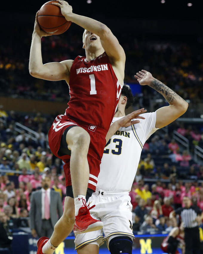 Wisconsin guard Brevin Pritzl (1) makes a layup as Michigan forward Brandon Johns Jr. (23) defends during the first half of an NCAA college basketball game Thursday, Feb. 27, 2020, in Ann Arbor, Mich. (AP Photo/Carlos Osorio)