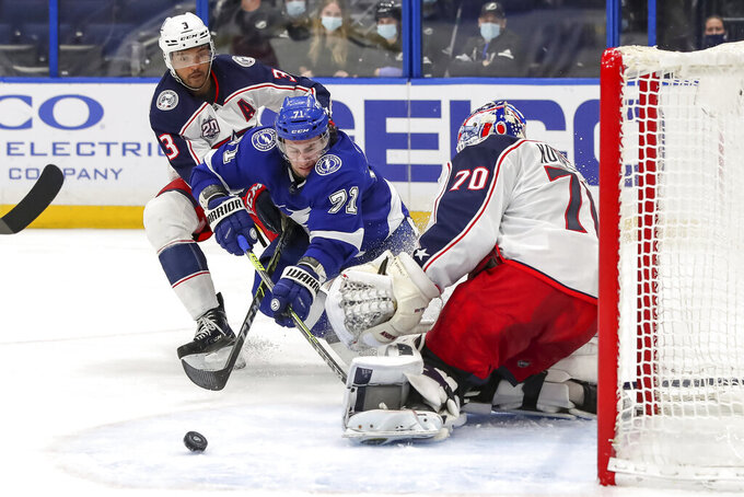 Columbus Blue Jackets goaltender Joonas Korpisalo (70), of Finland, makes a save against Tampa Bay Lightning's Anthony Cirelli (71) as Seth Jones defends during the second period of an NHL hockey game Sunday, April 25, 2021, in Tampa, Fla. (AP Photo/Mike Carlson)