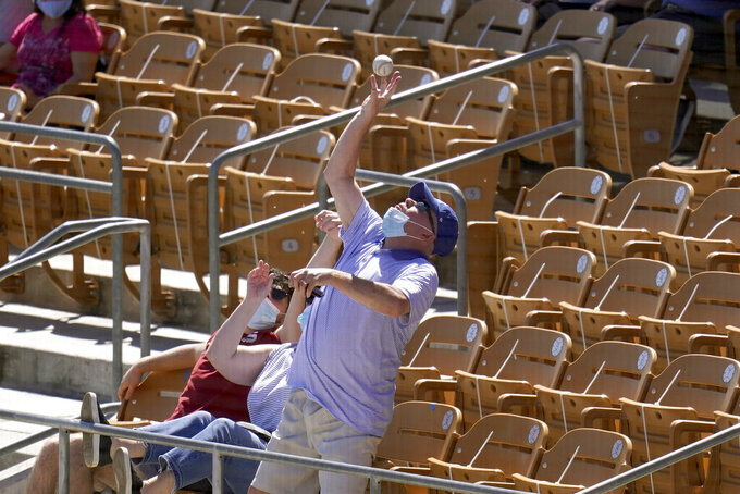 A fan reaches up to catch a foul ball hit by San Francisco Giants' Curt Casali during the fourth inning of the team's spring training baseball game against the Chicago White Sox on Monday, March 22, 2021, in Phoenix. (AP Photo/Ross D. Franklin)
