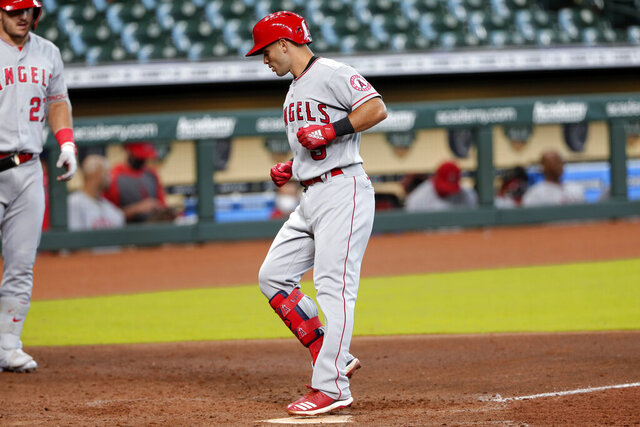Los Angeles Angels' Mike Trout, left, looks on as teammate Tommy La Stella (9) touches home plate after his home run during the sixth inning of the first game of a doubleheader baseball game against the Houston Astros Tuesday, Aug. 25, 2020, in Houston. (AP Photo/Michael Wyke)
