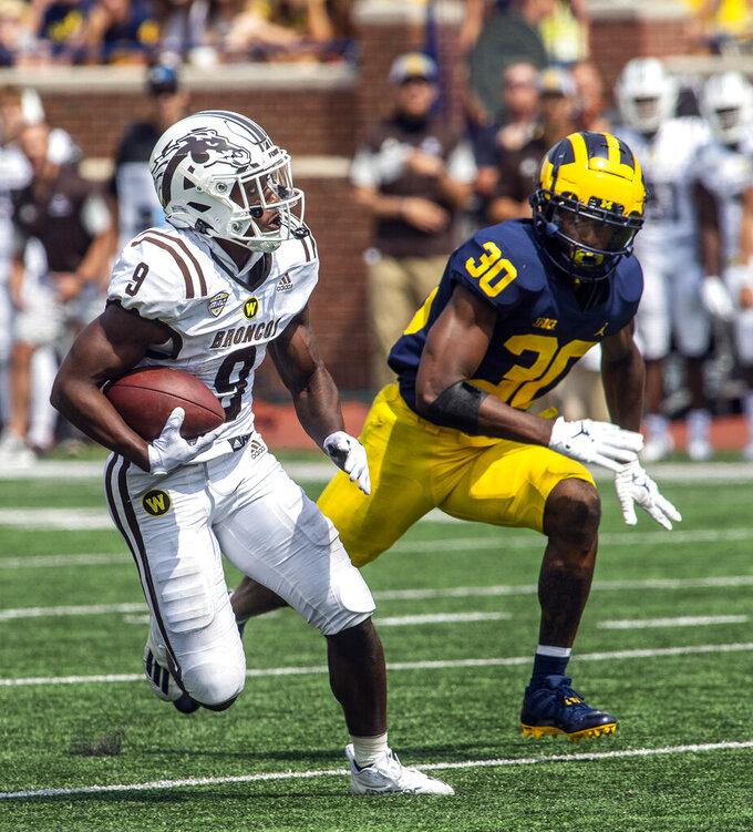 Western Michigan running back Sean Tyler (9) rushes against Michigan defensive back Daxton Hill (30) in the third quarter of an NCAA college football game in Ann Arbor, Mich., Saturday, Sept. 4, 2021. Michigan won 47-14. (AP Photo/Tony Ding)