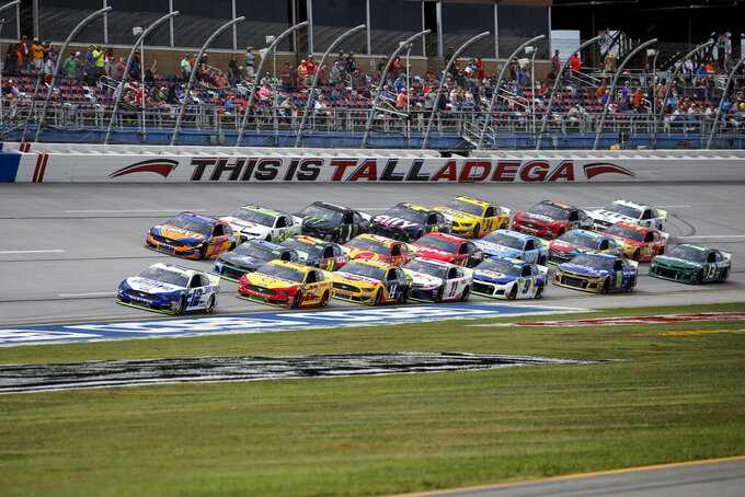 Ryan Blaney (12) leads a pack of cars through the tri-oval during a NASCAR Cup Series auto race at Talladega Superspeedway, Monday, Oct 14, 2019, in Talladega, Ala. (AP Photo/Butch Dill)