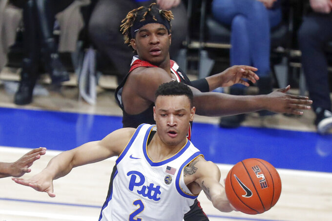 Pittsburgh's Trey McGowens (2) passes after getting around Northern Illinois's Eugene German during the second half of an NCAA college basketball game, Monday, Dec. 16, 2019, in Pittsburgh. Pittsburgh won 59-50. (AP Photo/Keith Srakocic)