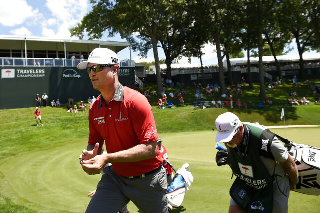 FILE - In this June 21, 2018, file photo, Zach Johnson walks off the 18th green during the first round of the Travelers Championship at TPC River Highlands in Cromwell, Conn. The tournament director for this week's Travelers Championship thought about encircling the 18th green at TPC River Highlands with giant video boards that could be filled with images of fans watching the golf and cheering from home. Thursday's, June 25, 2020, tournament will be held without fans, but is still expected to raise significant funds for charity. (John Woike/Hartford Courant via AP, File)