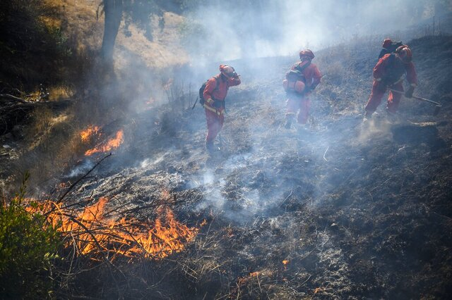 FILE - In this Thursday on Oct 24, 2019, file photo, an inmate hand crew works the fire line to fight a wildfire in Sonoma County near Geyserville, Calif. California is scrambling to find sufficient wildland firefighters amid a coronavirus outbreak that has depleted the ranks of inmates who usually handle some of the toughest duties. (Daniel Kim/The Sacramento Bee via AP, File)