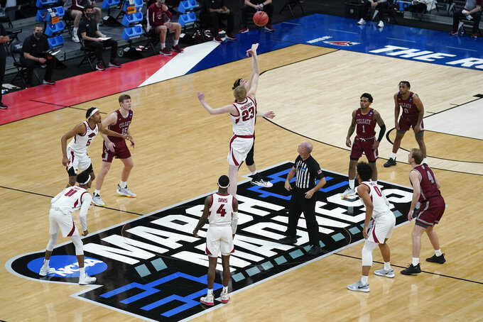 Arkansas' Connor Vanover (23) and Colgate's Keegan Records (14) tipoff for the start of a first round game at Bankers Life Fieldhouse in the NCAA men's college basketball tournament, Friday, March 19, 2021, in Indianapolis. (AP Photo/Darron Cummings)