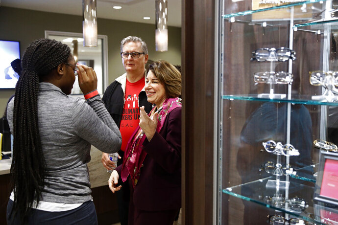 Democratic presidential candidate Sen. Amy Klobuchar, D-Minn., speaks with a patient trying on glasses as she tours the Culinary Health Center, Friday, Feb. 14, 2020, in Las Vegas. Standing with Klobuchar is Culinary Union president Ted Pappageorge. (AP Photo/Patrick Semansky)