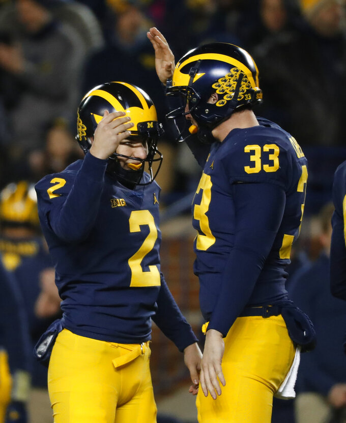 Michigan place kicker Jake Moody (2) celebrates kicking a 29-yard field goal with long snapper Camaron Cheeseman (33) in the second half of an NCAA college football game against Indiana in Ann Arbor, Mich., Saturday, Nov. 17, 2018. Michigan won 31-20. (AP Photo/Paul Sancya)