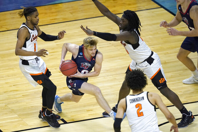 Liberty's Drake Dobbs (0) drives between Oklahoma State guard Rondel Walker (5) and Isaac Likekele, right, during the second half of a first round NCAA college basketball game Friday, March 19, 2021, at the Indiana Farmers Coliseum in Indianapolis.Oklahoma State won 69-60. (AP Photo/Charles Rex Arbogast)