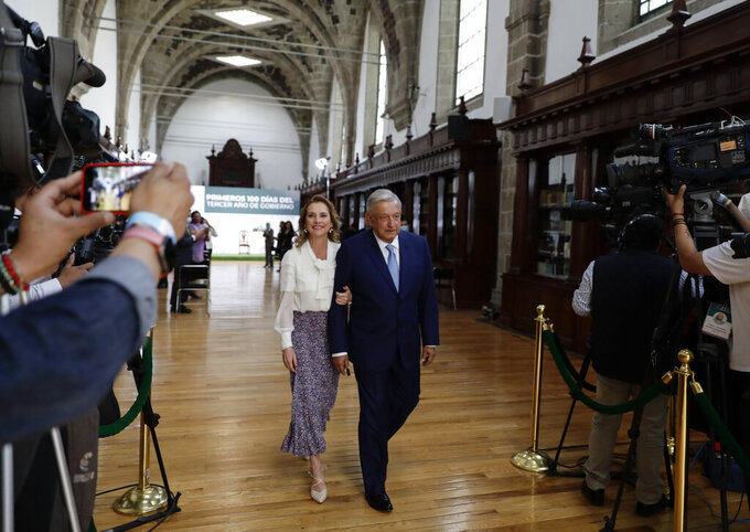 Mexican President Andres Manuel Lopez Obrador and his wife Beatriz Gutierrez leave the National Palace after a news conference to mark the 100th day of his third term in office, in Mexico City, Tuesday, March 30, 2021. (AP Photo/Eduardo Verdugo)
