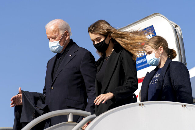 Democratic presidential candidate former Vice President Joe Biden, accompanied by his granddaughters Maisy Biden, right, and Natalie Biden, center, arrives at Flint Bishop International Airport in Flint, Mich., Saturday, Oct. 31, 2020, for a rally with former President Barack Obama. (AP Photo/Andrew Harnik)
